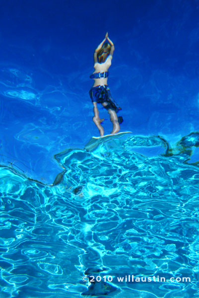 Boy on diving board above pool from underwater