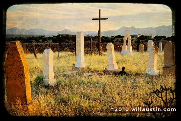 Grave markers and cross at the Old Galisteo Cemetery in Galisteo, New Mexico at sunset