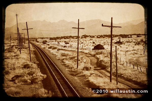 Train tracks receding into the distance with the Sandia Mountains in the far distance, near Santa Fe, New Mexico