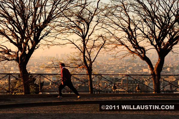 Jogger stretches with a view of Paris from the Sacré-Cœur Basilica