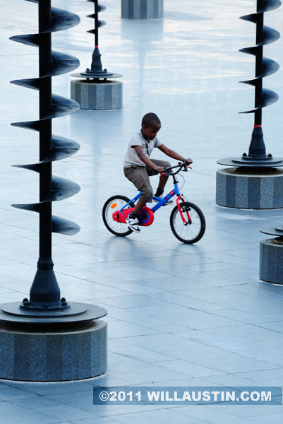Child riding bike in an empty fountain at La Defense in Paris, France