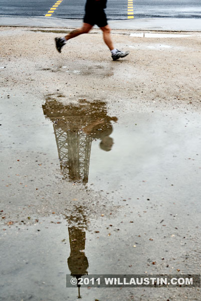 Eiffel Tower and runner reflected in a puddle