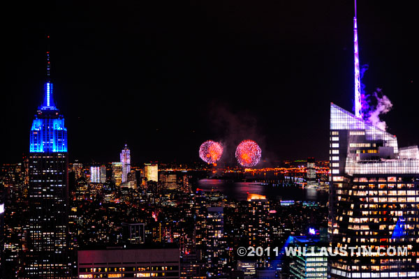 New York City skyline at night with fireworks for 150th anniversary of the Statue of Liberty