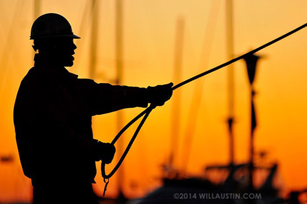 Construction worker holding cable at sunset by Will Austin Photography