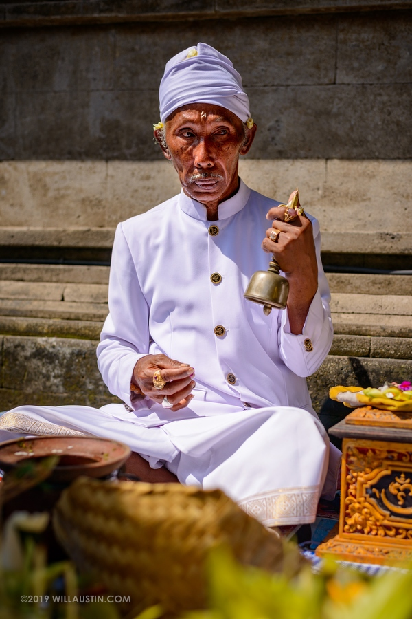 Hindu priest ringing bell at a temple in Bali