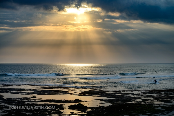 Surfers and waves at sunset in Bali near Canggu