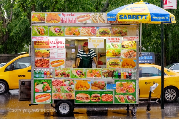 Falafel stand in the rain with taxis in New York near Central Park