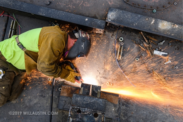 Worker using a cutting torch to cut steel on a barge
